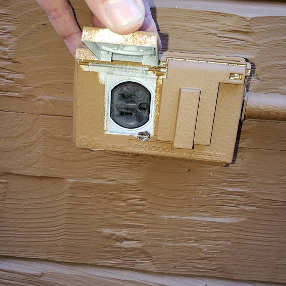 Exterior outlet being checked for seals and safety on Westminster Home Inspection